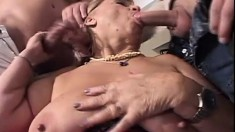 Big-breasted old hooker sits on one cock and suckles another with great pleasure