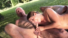 Playful young babe has two lustful old guys sharing her pussy outside