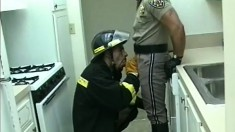 Nasty fire-fighter shoves his dirty cock in the mouth of police officer