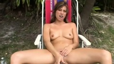 Seductive brunette with sexy tits has fun with a glass dildo outside