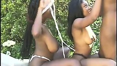 Three black cuties hook up outside and have some lesbian fun with a strap-on dildo